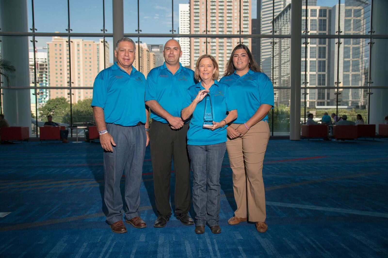 4 Laguna Vista employees in blue shirts with one holding award at event