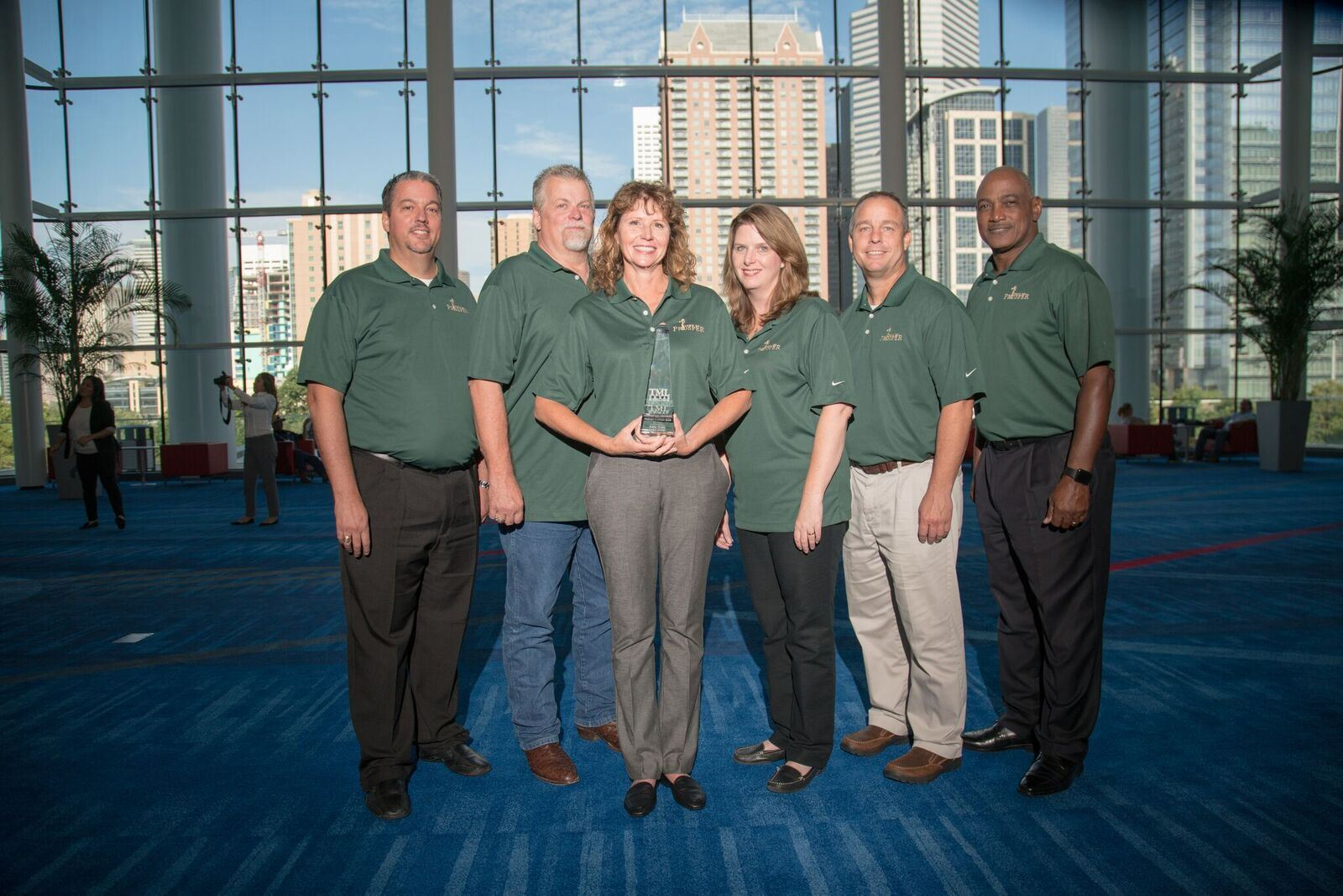 6 Prosper employees in green shirts together with one holding award at event