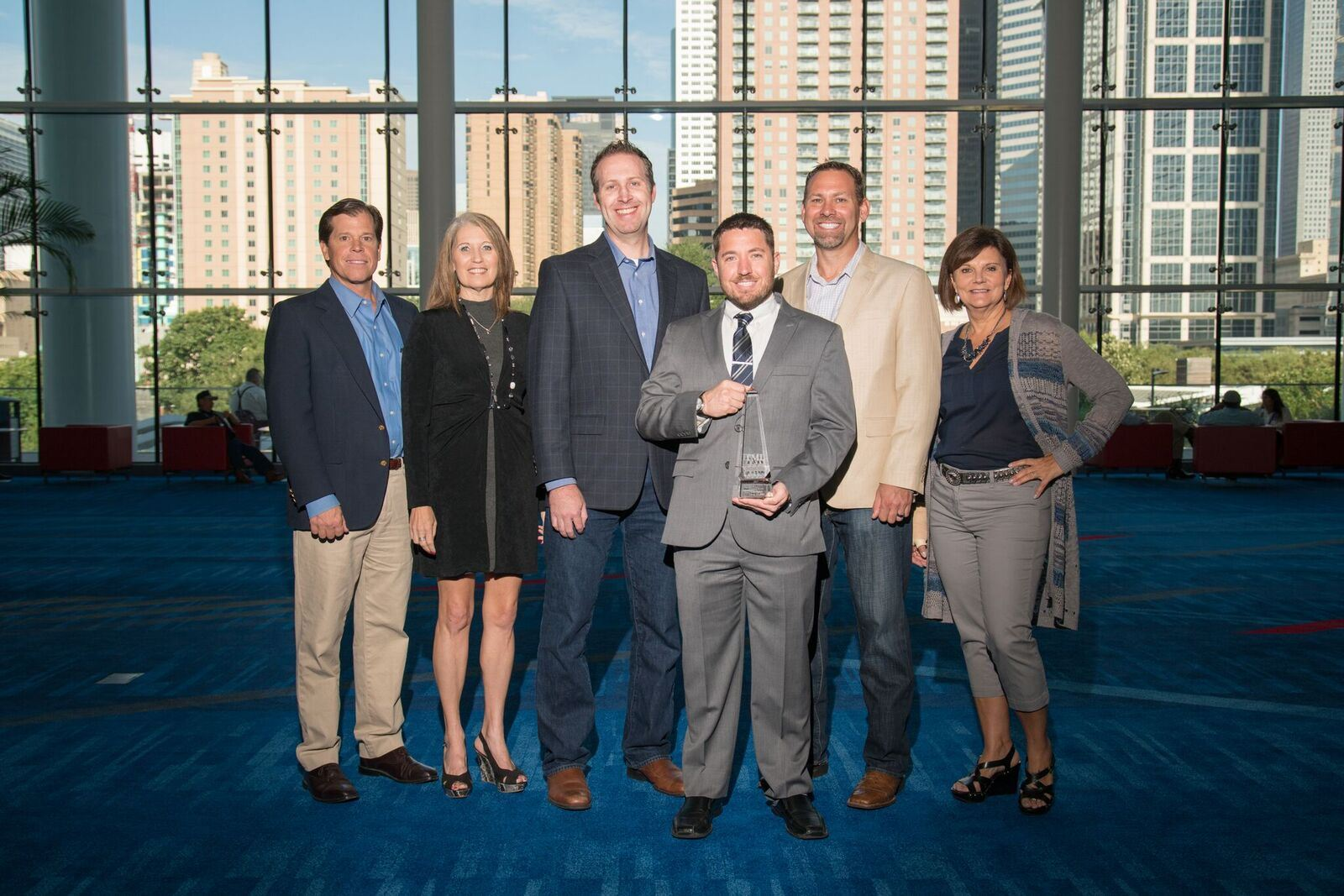 6 Round Rock employees together with one holding award at event