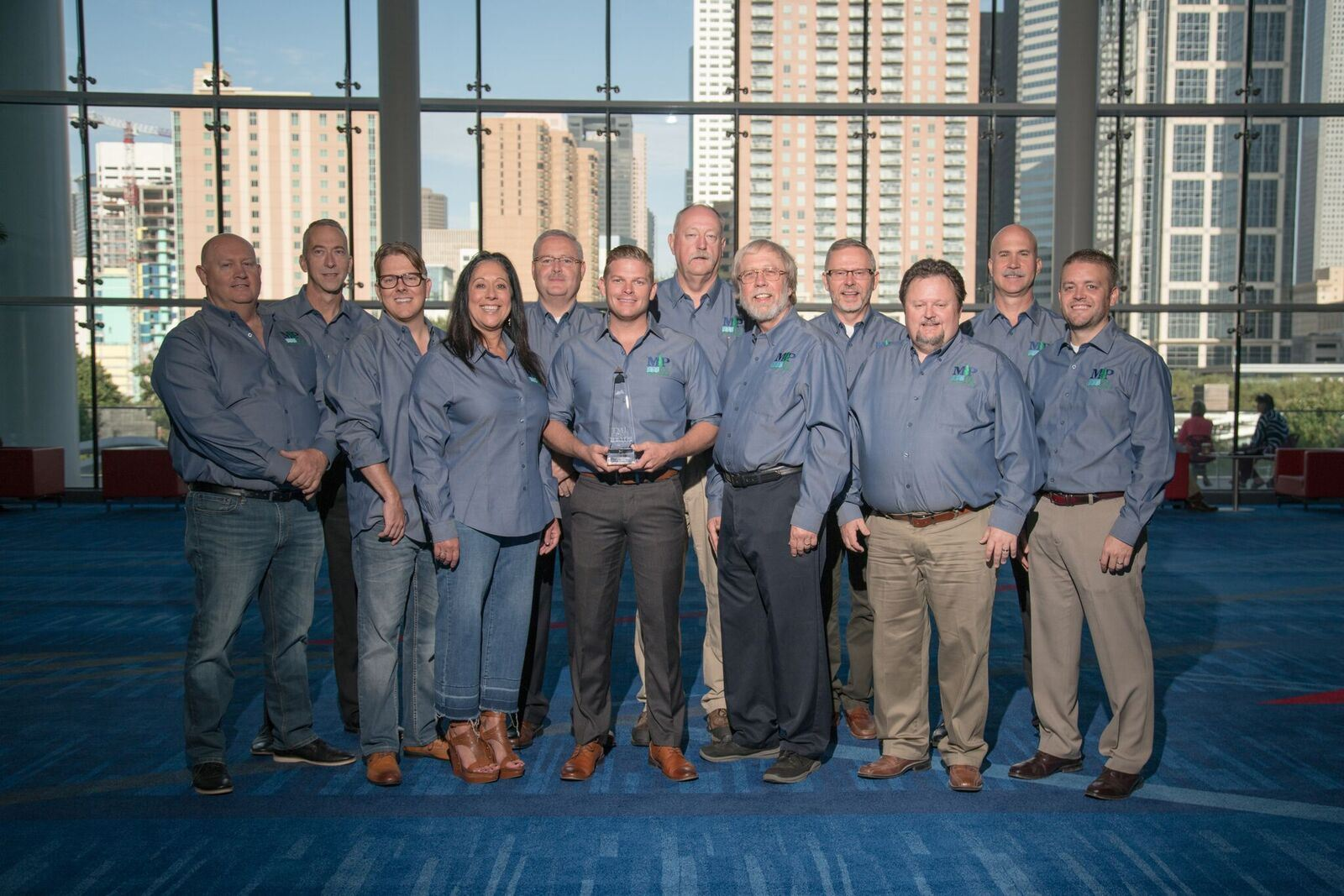 12 Mount Pleasant employees in blue shirts with one holding award at event