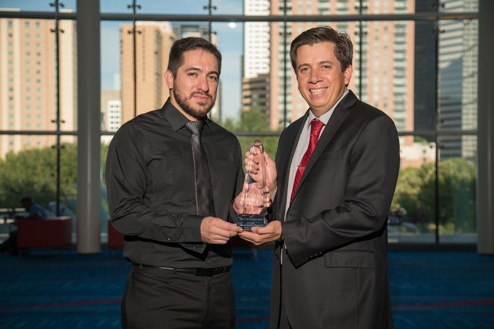2 El Paso employees together holding award at event