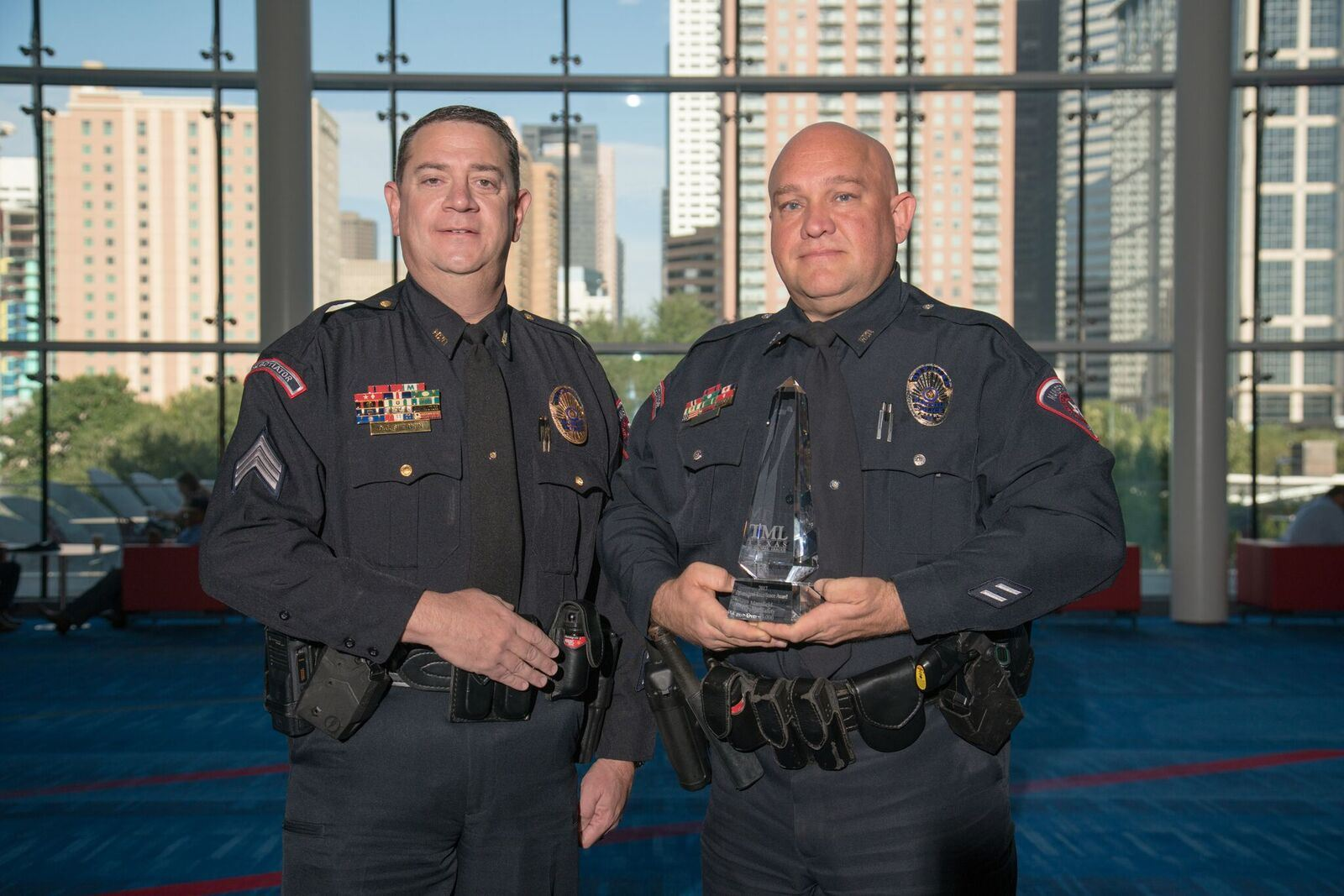 2 Mansfield officers together with one holding award at event